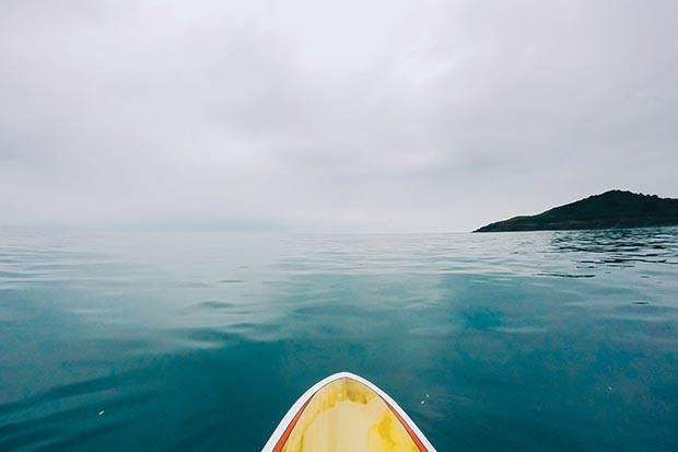 A surf board on the still ocean in Wales