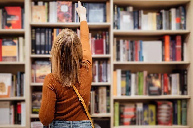 Woman reaching for a book on a shelf