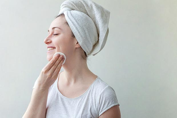 Woman removing makeup wearing a towel on her head