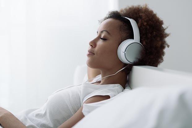 Woman relaxing and listening to a podcast
