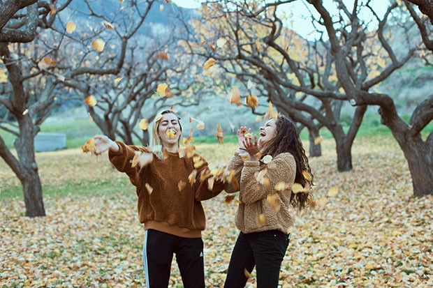 Women throwing autumn leaves in the air