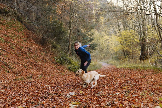 Woman playing fetch with her dog in the woods