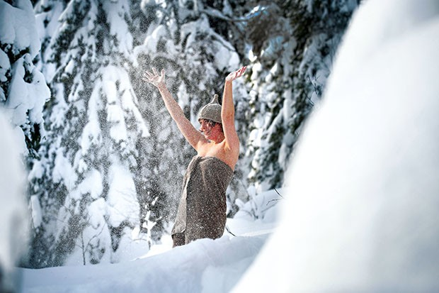 Woman throwing snow in the air after a sauna