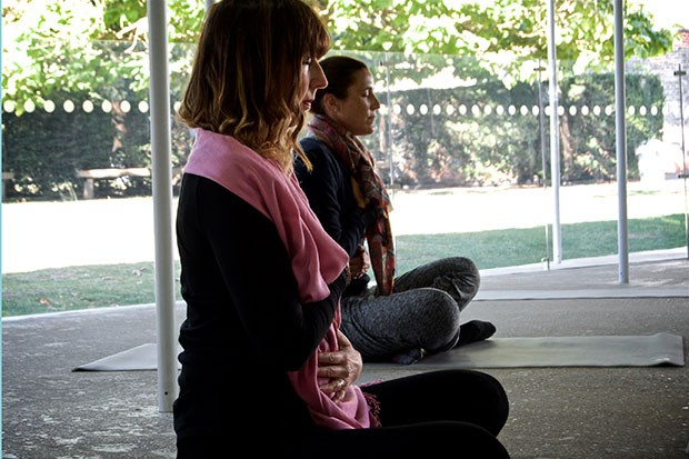 Two women meditating at the Serpentine Pavilion