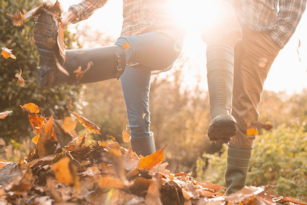 A couple kicking up autumn leaves wearing wellington boots
