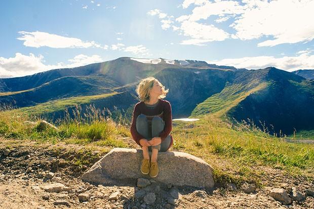 Woman sitting on a mountain top enjoying the sunshine