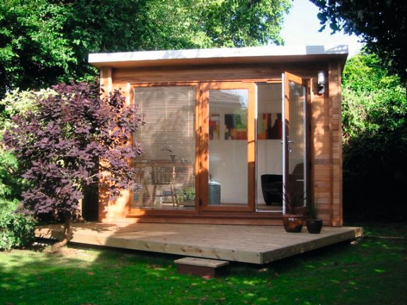 A rectangular wooden shed offers a light and airy office space in the garden.