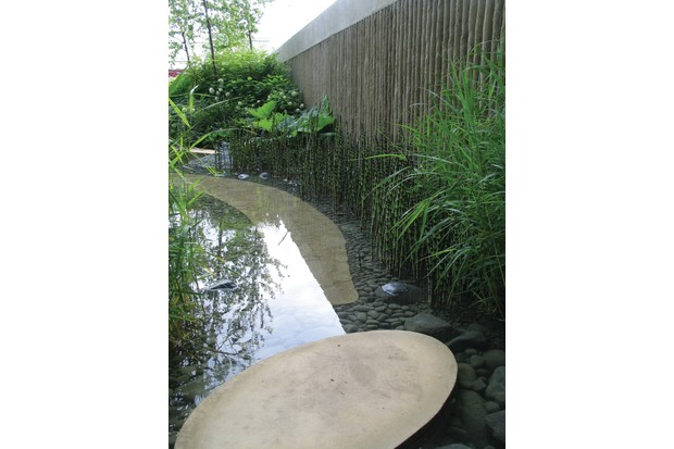 Natural water tank with pebble flooring, surrounded by green shrubbery