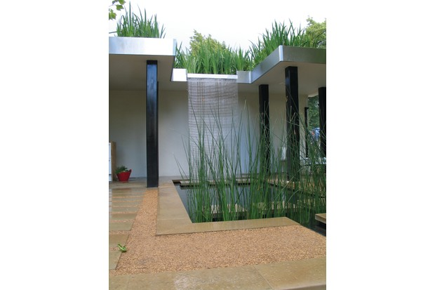 A modern designed reed bed with waterfall and greenery