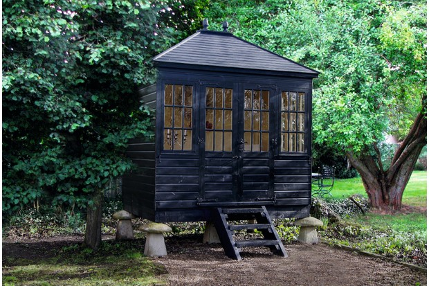 A traditional garden studio mounted on saddle stones resembles an old grain store
