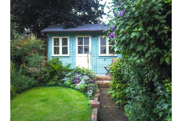 A bright blue garden cottage style shed is situated at the bottom of a garden with a leading plan and tree surrounds