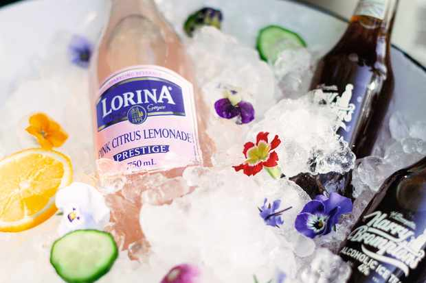 A large container of ice keeps a pink bottle of lemonade chilled with freshly chopped oranges, cucumbers and edible floral and foliage garnishes