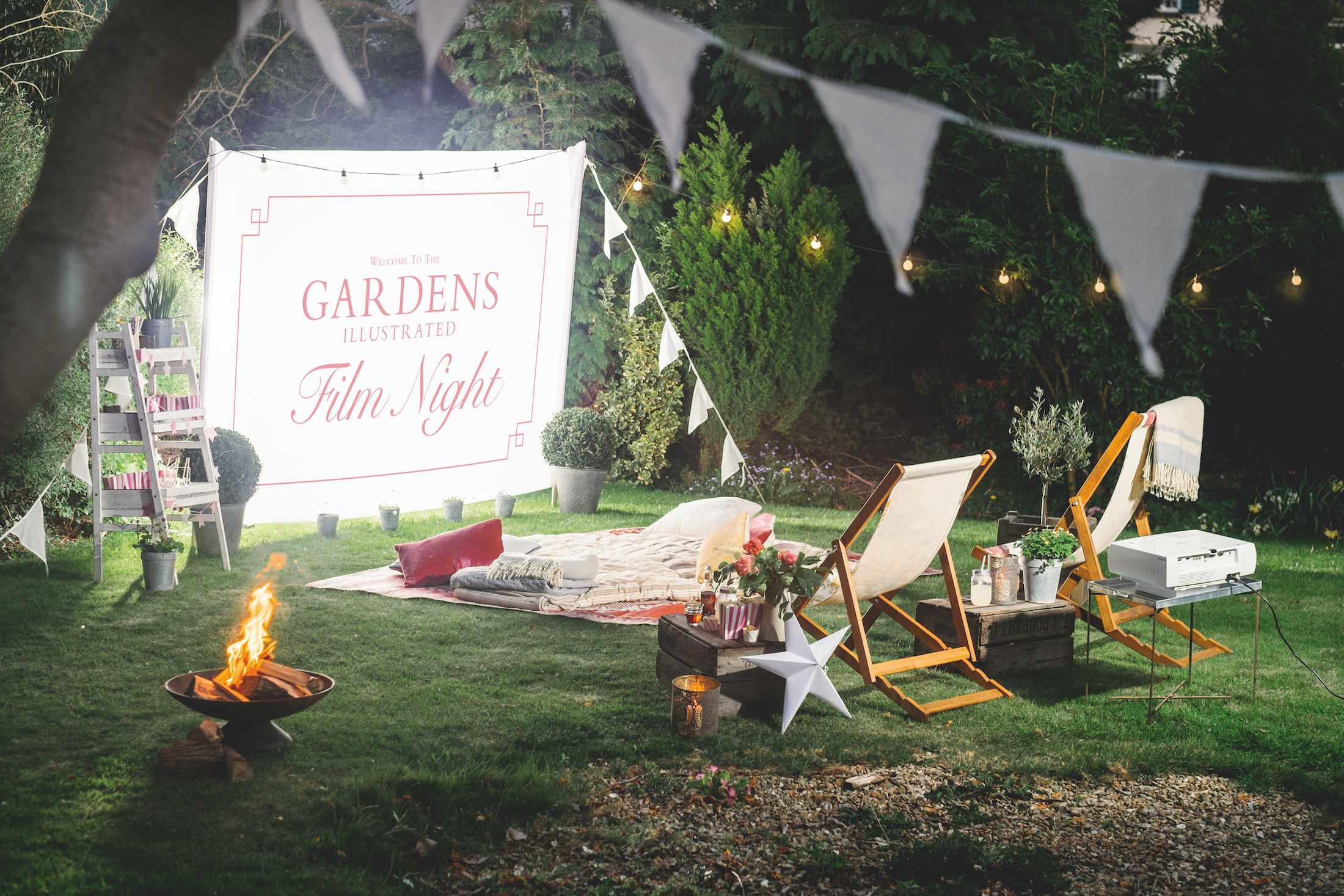 An outdoor cinema set up in a domestic garden complete with snack trolley, fire pit and deck chairs to help with the entertainment