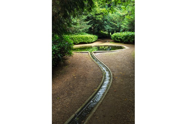 A paved area with a serpentine rill leads running water to a tranquil and still pond surrounded by greenery and trees