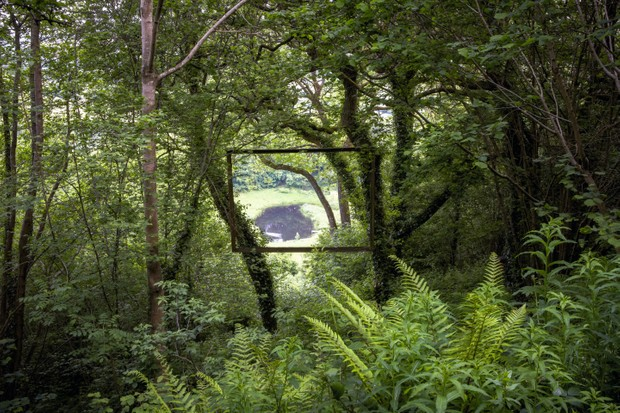 A frame hangs high within trees to offer a tantalising glimpse of another garden episode – a lakeside meadow in the valley below.