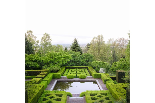 Formal knot garden with relaxed woodland garden on hillside below