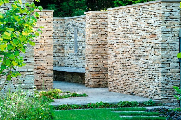 A tall dry-stone wall behind neatly trimmed green grass, in a Cotswold rectory garden