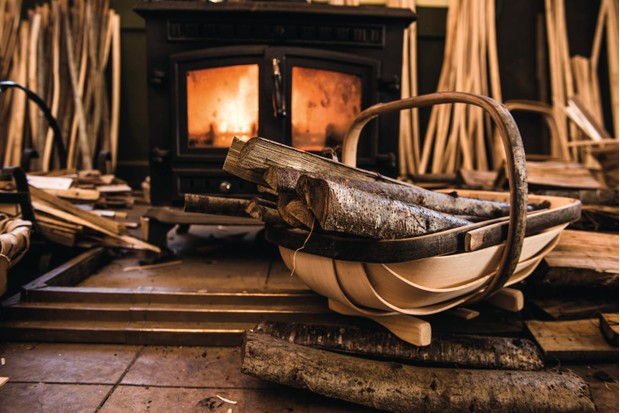 The Royal Sussex Fireside Log Trug carrying logs placed in front of lit wood burner