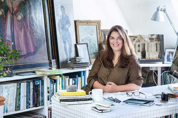 Designer Jinny Blom sits at her desk in front of a filled bookcase and antique paintings