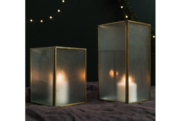 Frosted glass and brass lantern with large lit candle inside offering a diffused glow