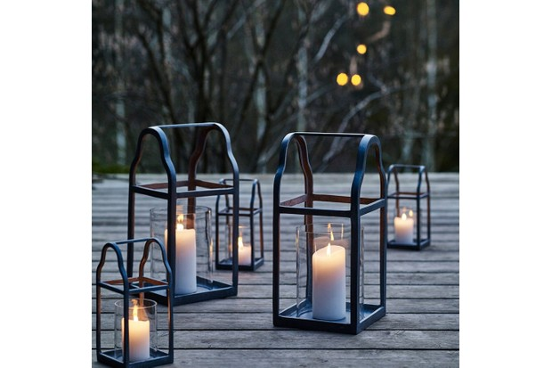 Cast from zinc, an outdoor garden lantern with curved gabled roof holds a lit candle on wooden decking