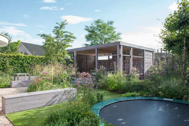 A garden for the whole family to enjoy featuring a garden room and trampoline has been designed by Garden Designer Carrie Preston