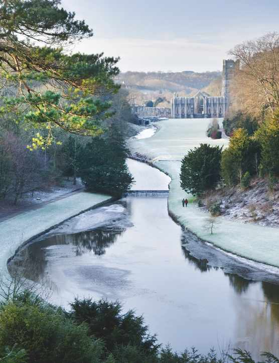 Looking over the Half Moon Pond and weir of Studley Royal Water Garden in winter from the Surprise View towards Fountains Abbey, North Yorkshire.