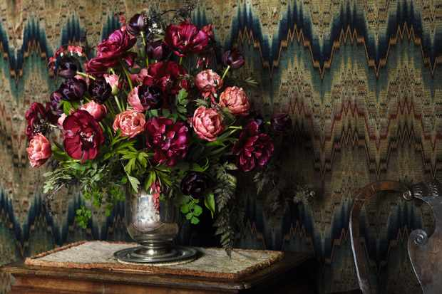 A photograph depicting a sumptuous floral arrangement of tulips in contrasting colours of deep reds, dark purple and light pink