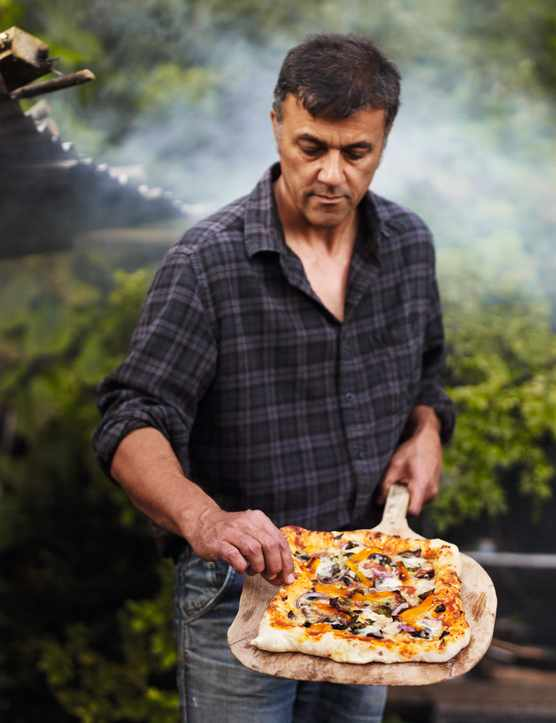 A pizza that has been cooked over a campfire has been placed on a wooded utensil and is ready to serve