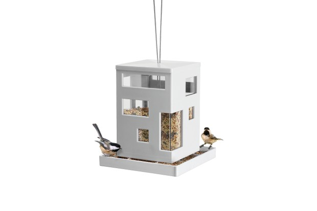 Stylish bird feeder that looks like a building with two birds eating from the base