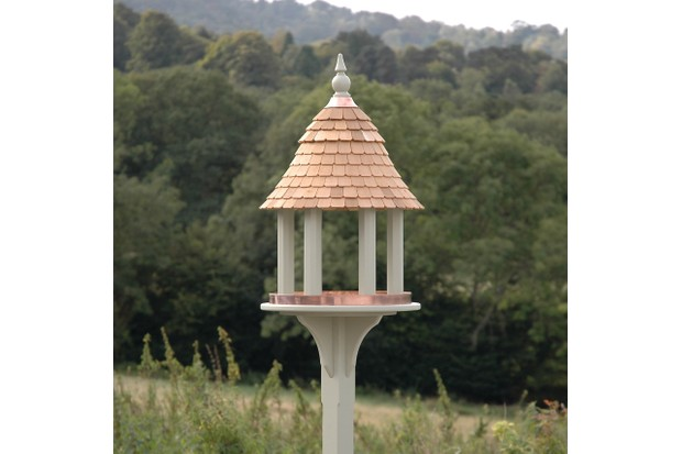 A traditional bird table painted in an olive green shade