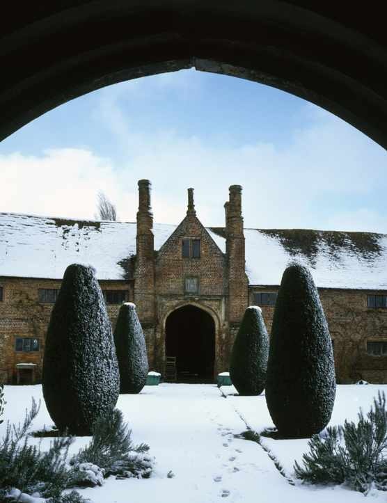 A winter view at Sissinghurst Castle Garden, Kent, through the arched Tower entrance towards the front range, dating from about 1490