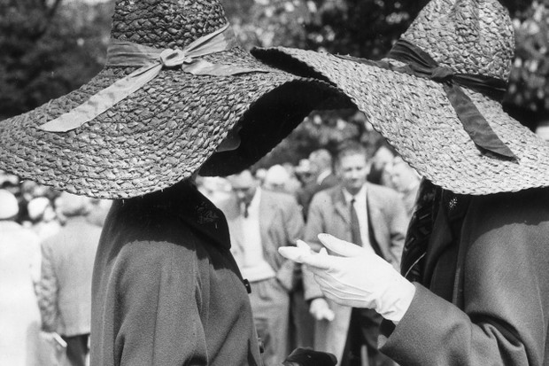Two women wearing large, floppy brimmed, straw hats have a chat during a visit to the Chelsea Flower Show in 1963.