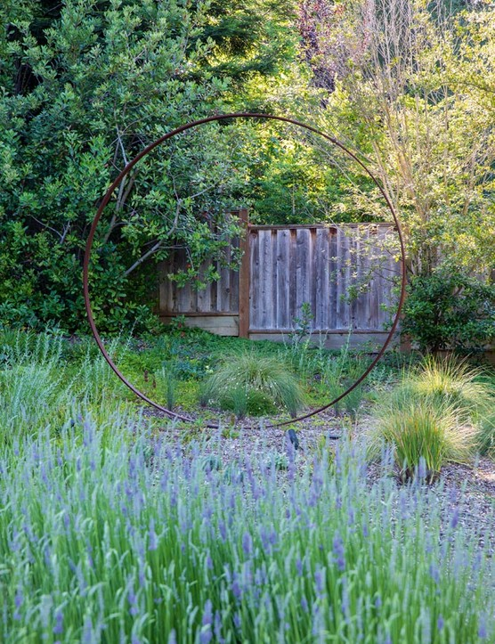 A sculptural metal ring creates a moon-gate effect at the border of the property