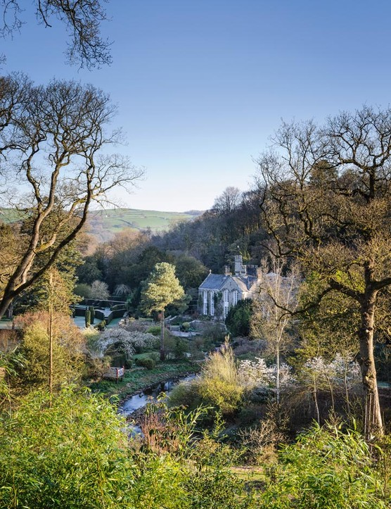 Gresgarth Hall sits at the mouth of a wooded valley, with the brook Artle Beck drawing a sweeping curve as it rushes past the house. Dark yew hedges stamp formality near the house and echo the stone walls etched on the hills beyond.