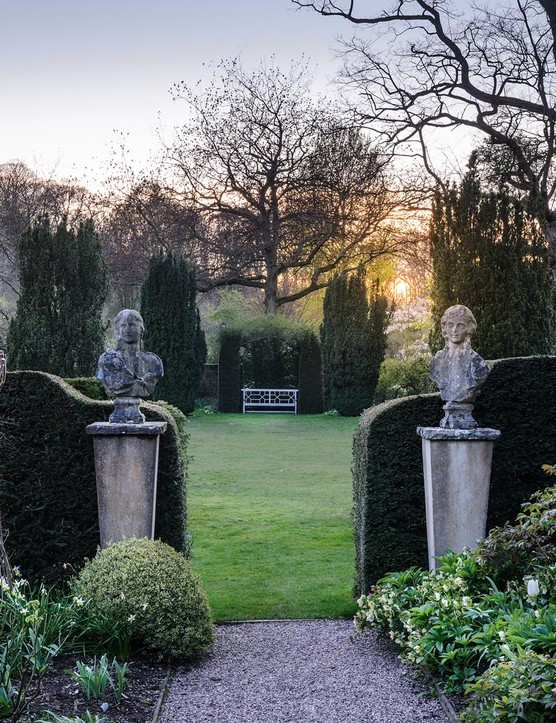 Tightly clipped yew hedges carry the architecture of the house into the garden, providing shelter and formality, and divide the garden into separate rooms and corridors. Here, a pair of Janus statues marshal the transition from one space to the next.