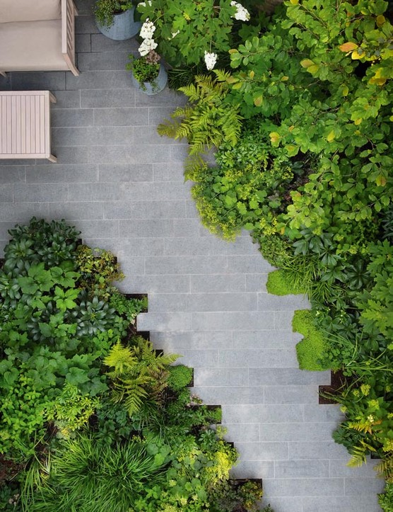 The planting, built up in layers, spills over the edges of the paving, softening the effect.