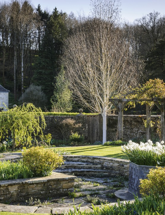 In the walled garden, the weathered timber pergolas that line two sides of the walkway are covered in climbing roses and clematis. The sunken central section in the quatrefoil shape features a large, octagonal metal planter.