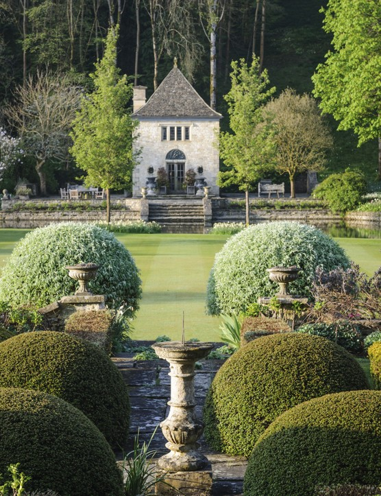 The old stone sundial is flanked by clipped Pyracantha domes. It lines up perfectly along the axis from the back door, down the steps and lawn, and across the river to the extraordinary summerhouse.