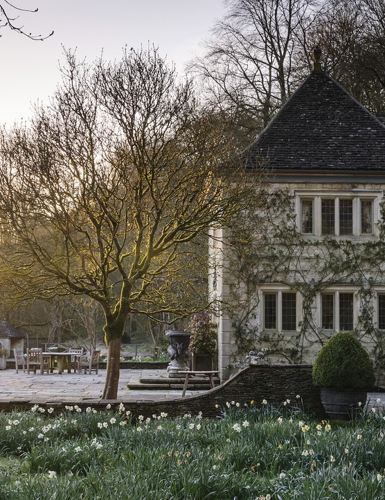 The summer house and its sun-filled terrace are the final elements of formality before the garden segues into a more naturalised feel surrounded by swathes of daffodils and other spring bulbs that extend down from the bank of woodland behind.