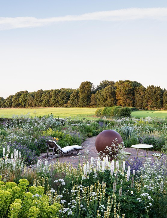 The sphere that sits at the centre of the garden is from Capital Garden Products and was designed by the owner's cousin. Though it looks as if it's made from metal, it is in fact fibreglass, meaning it is light and can easily be moved. It tones well with the paving and the russet tone of the bronze fennel.