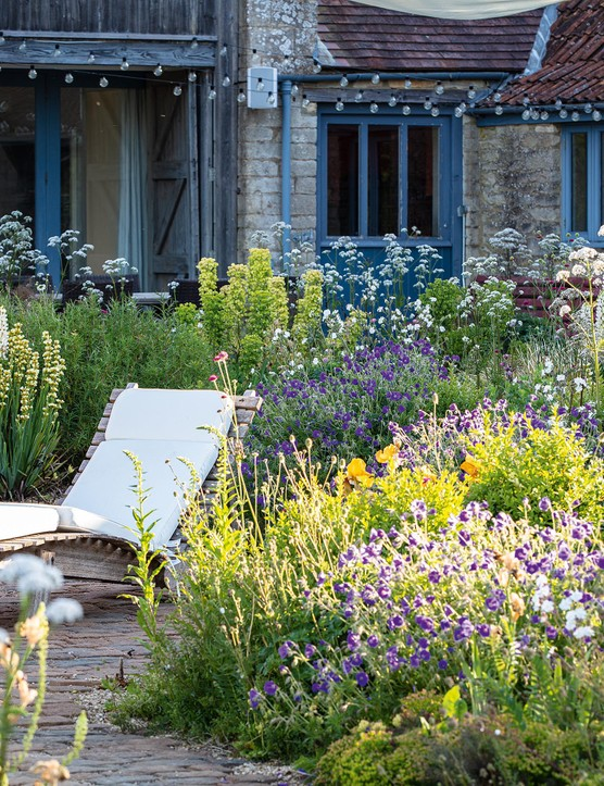 For James, plants fall into two camps, 'architectural' and 'fluff', the latter bringing romance and soul. The 'fluff' here is a mix of Geranium Rozanne (= 'Gerwat'), Silene latifolia and Digitalis lutea in front of the lounger. A self-seeded poppy is a reminder of the garden's past as a wildflower meadow.