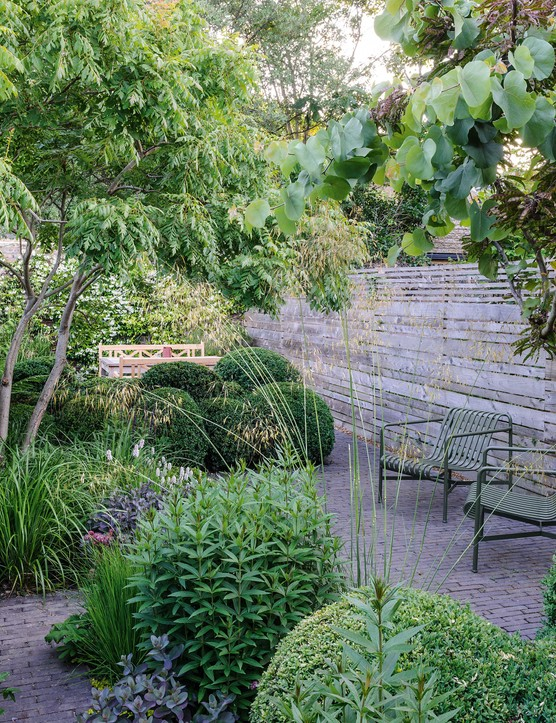 Devoid of planting, a wooden fence is a foil to the busy melee of planting. Exuding a sense of calm, it keeps the balance of the garden in check. See-through furniture contributes to a seamless flow from one end of the garden to the other.