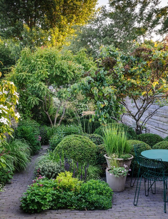 Designer Emily Erlam has created a gentle journey along a plum-coloured brick path that winds its way via intimate seating areas among a mass of evergreens and shrubby trees underplanted with perennials, grasses and bulbs.