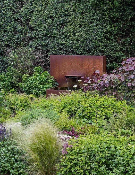 The contemporary water feature makes an arresting focal point in this plant-heavy garden, surrounded by green foliage dotted with the lacy, white flowers of Cenolophium denudatum. The sound of falling water adds to the feeling of calm and serenity that pervades this wonderful space.