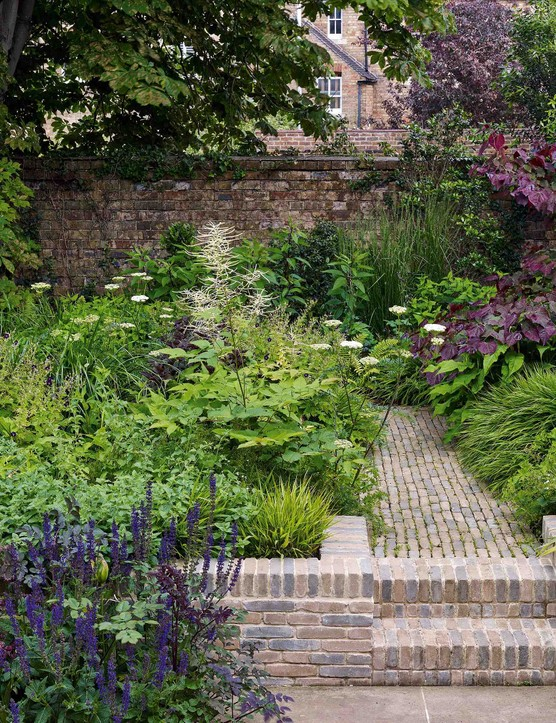 The deep beds are crammed with a complex tapestry of perennial interest, with an emphasis on foliage that ranges from the fresh, grassy growth of Hakonechloa macra to the deep-plum leaves of Cercis canadensis 'Forest Pansy'.