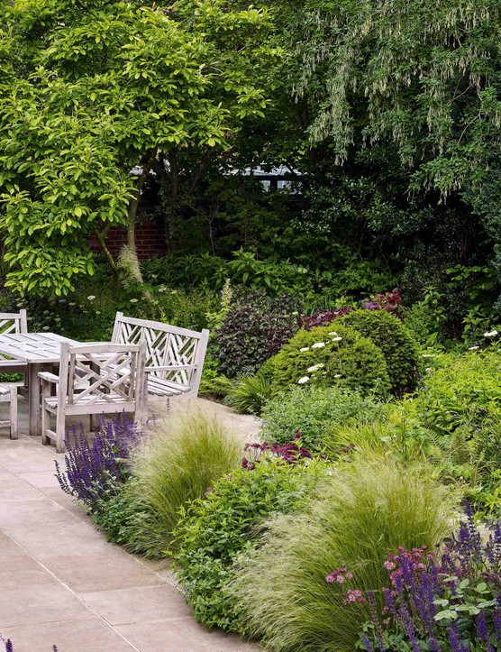 The spacious dining terrace is in the sunniest part of the garden, shielded from overlooking windows by a stand of trees that includes a large magnolia. Ornamental grasses and the deep-amethyst flower spikes of Salvia x sylvestris 'Mainacht' soften surrounding beds anchored with plump balls of yew.