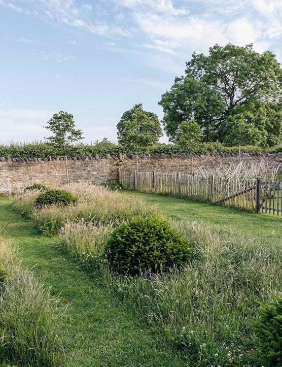 The Willow Garden, a simple but effective grid of rumpled yew domes set in long grass with an inviting bench that catches the evening sun. Beyond the paling fence is the Vegetable Garden.