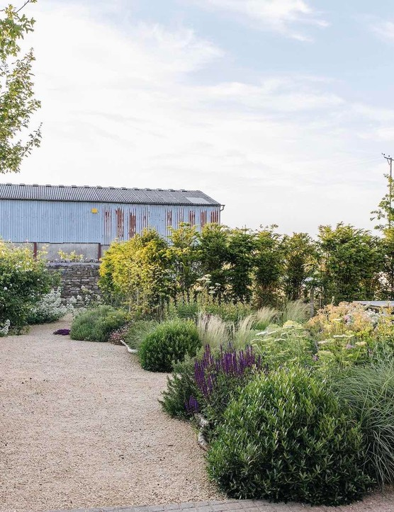 The path leading to the Gravel Garden, with the Farrowing House on the right and a wall made from recycled stone on the left. A corrugated iron silage barn provides protection from the wind. One of four field maples planted for shelter frames the view beyond.