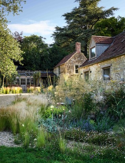 In the gravel garden at the side of the house, Jo has used a planting palette that complements the house's Cotswold stone with grasses, such as Stipa tenuissima, and perennials including Verbascum bombyciferum 'Polarsommer' and oreganums. This sunny space also includes a greenhouse for propagating plants and a couple of raised beds for vegetables.